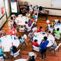 An overhead view of a group of kids eating in the dining hall.
