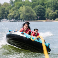 Two girls scream as they ride a tube behind a boat.