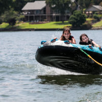 Two girls hang on while their tube gets a little air born while being towed by a boat.