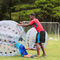 A camp counselor pushes a camper in a bubble soccer ball.