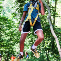 A counselor hangs from a tree in a harness on the ropes course.