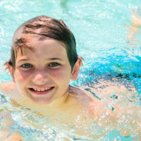 A young boy smiles at the camera while swimming in the pool.