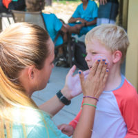 A camp counselor applies sunscreen to a young camper.