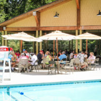 A group sits poolside under outdoor umbrellas.