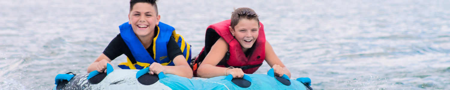 Two boys smile as they ride on an inflatable tube being towed by Camp Canaan's boat.