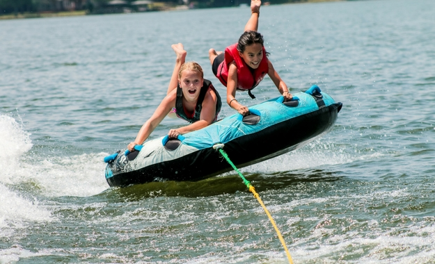 Two girls ride on an inflatable tube that's being pulled by a boat on the Catawba river.