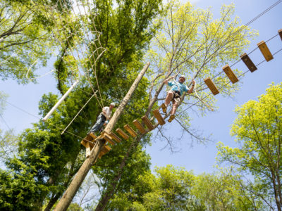 A man walks across the high ropes course at Camp Canaan during a team building exercise.