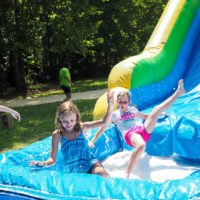 Two girls slide down an inflatable slide into a shallow pool of water.