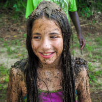 A girl covered in mud smiles.