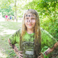 A young girl in a lime green shirt covered in mud.