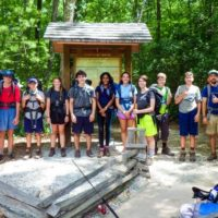 A group of teens wearing back packs pose before starting a hike.