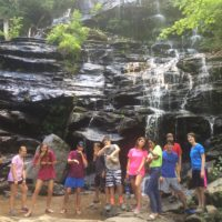 A group of teens pose in front of a waterfall.