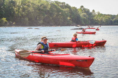 A girl smiles while kayaking in the shallows of the Catawba River.