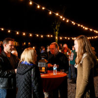 Two men and two women gather around a table chatting at a night event under a string of lights.