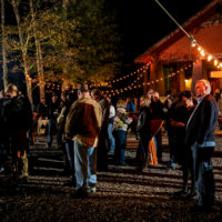 A group socializes outside during a night event at Camp Canaan.