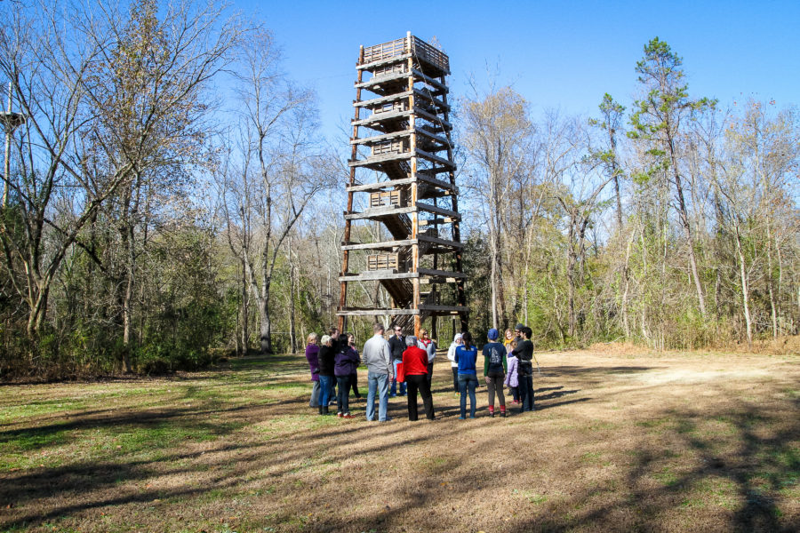 A group of people pose in front of the tower at Camp Canaan.