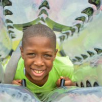 A young boy smiles looking through the center of his bubble soccer ball.