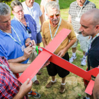 A group assembles a paper and cardboard plane during a team building exercise.