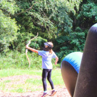 A girl watches her arrow soar through the air during a game of archery tag.