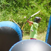 A young boy in a lime green tee shirt about to launch an archery tag arrow.