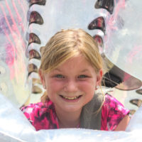 A young girl smiles from the inside of her bubble soccer ball.