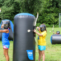 Two girls take aim in a game of archery tag while standing next to an inflatable barrier.