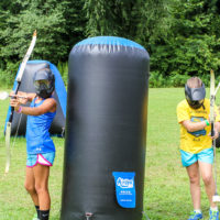 A girl takes aim while hiding behind an inflatable barrier during a game of archery tag.