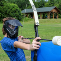 A boy wearing a protective mask takes aim with his arrow in a game of archery tag.