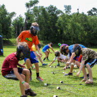 A group of kids races to pick up arrows to begin a game of archery tag.