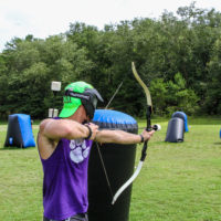 A teenager in a purple tank top takes aim with his bow and arrow during a game of archery tag.