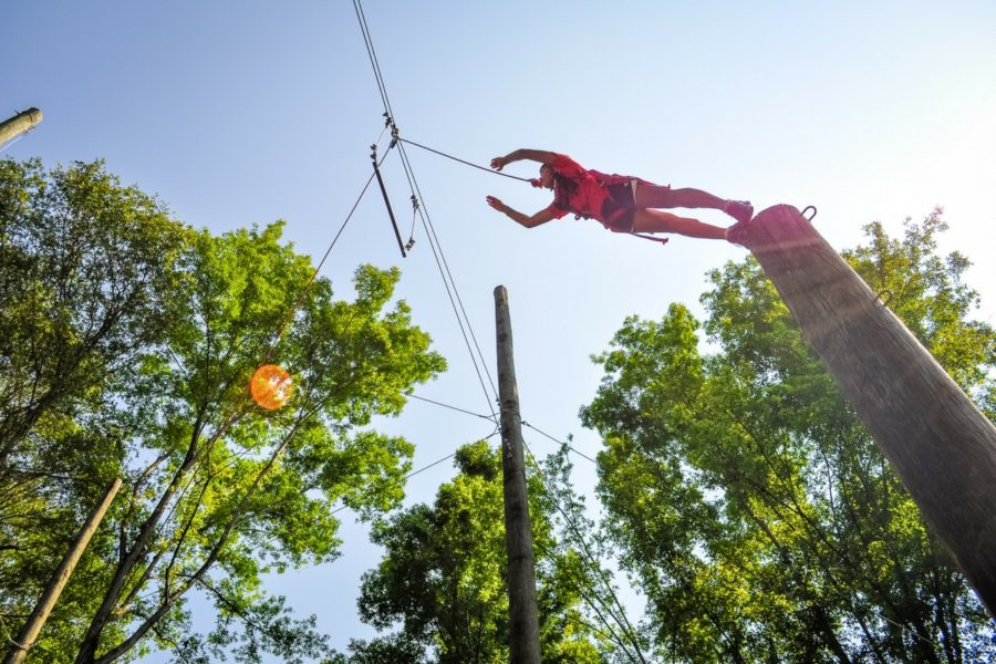 A young girl leaps from a column towards a hanging bar on the Leap of Faith jump at Camp Canaan.