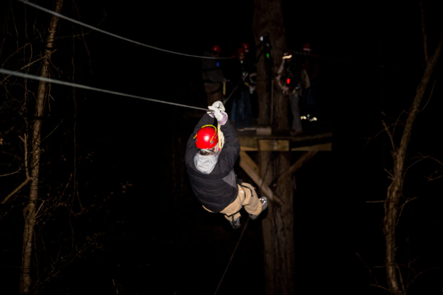 A man glides down a zip line wearing a red helmet in the pitch black participating in the Night Zip Canopy Tour.