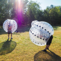 A group of three play a game of bubble soccer.
