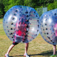 Two people collide wearing bubble soccer balls.