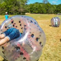 A girl attempts to get into a bubble soccer ball at Camp Canaan.