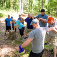 A group holds on to each other in a team building exercise at Camp Canaan.