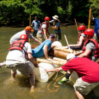 A group puts their homemade raft in the Catawba River during a team building session at Camp Canaan.