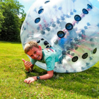 A young boy hangs out of his bubble soccer ball and gives a thumbs up.