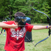 A teenager in a red tee shirt takes aim with his bow and arrow during a game of archery tag.
