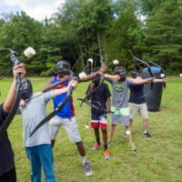 A line of kids shoot archery tag arrows into the air.